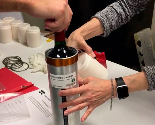 Researchers with Space Cargo Unlimited prepare bottles of French red wine to be flown aboard a Northrop Grumman capsule from Wallops Island, Va., to the International Space Station on Nov. 2.