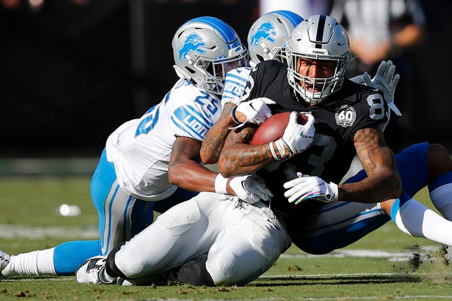 Raiders tight end Darren Waller is tackled by Detroit Lions defensive back Will Harris (25) and cornerback Darius Slay during the first half.