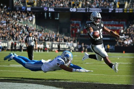 Raiders running back Josh Jacobs (28) runs for a touchdown past Lions defensive back Miles Killebrew during the first half on Sunday.