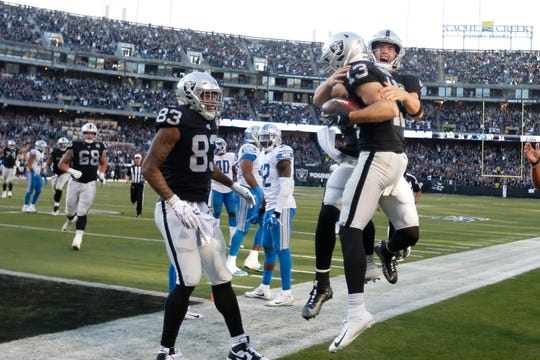 Oakland Raiders wide receiver Hunter Renfrow (13) celebrates with quarterback Derek Carr, right, after they connected on a touchdown pass against the Detroit Lions in the fourth quarter.