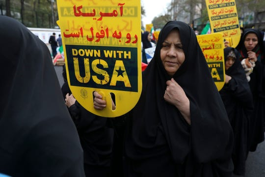 A demonstrator holds an anti-U.S. placard during an annual rally outside the former U.S. Embassy in Tehran, Iran, Monday, Nov. 4, 2019.