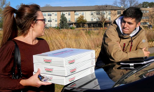 On this Saturday, October 26, 2019, photo, left, Catherine Newton buys three boxes of Krispy Kreme donuts from Jayson Gonzalez in Little Canada, Minn.