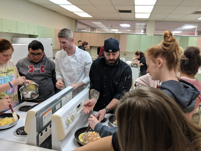 Catawba Island Club chefs Addison Hoover and Ron Webb (center) help Port Clinton High School students learn real life skills making delicious omelets.