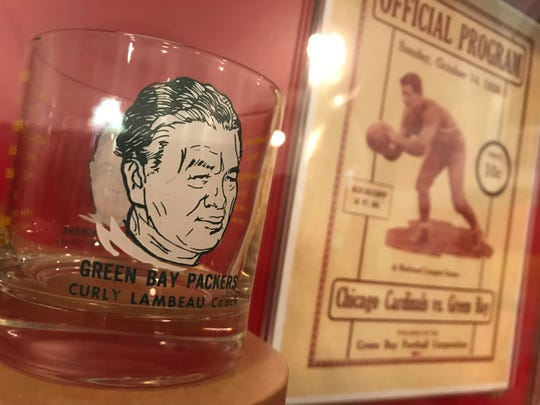 "A souvenir glass with Curly Lambeau's face depicted on it and a Green Bay Packers game program from 1928 are among the artifacts on loan from the Green Bay Packers Hall of Fame for ""The Bellicose Belgian"" exhibit celebrating Lambeau's heritage at the Belgian Heritage Center in Brussels, Wisconsin."
