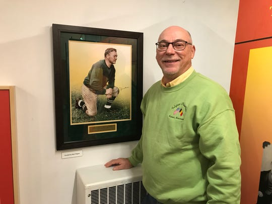 "Belgian Heritage Center board member Bill Chaudoir with a portrait of Curly Lambeau, part of ""The Bellicose Belgian"" exhibit at the center in Brussels, Wisconsin celebrating the roots of the Green Bay Packers founder."
