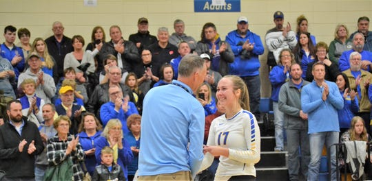 As fans of the Blue Devils applaud, Oconto senior Aubree Bucheger smiles as she collects her sectional runner-up medal from St. Mary Catholic High School Athletic Director Matthew Schoultz after the sectional final against Fall Creed on Saturday, Nov. 2, at St. Mary Catholic High School in Neenah.