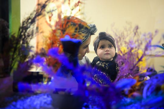 Hailie Hyman looks at a fish tank with her daughter Maci, 1, before an appointment at the Prisma Health Pediatric Hematology Oncology Center Monday, Nov. 4, 2019.