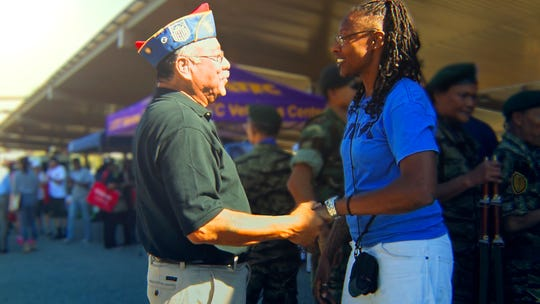 """Iraq War veteran Tracey Cooper Harris (right) greets a veteran at a Veterans Day parade she helped organize in Los Angeles, California. Cooper-Harris is featured in the WORLD Channel Documentary, """"Surviving Home."""""""