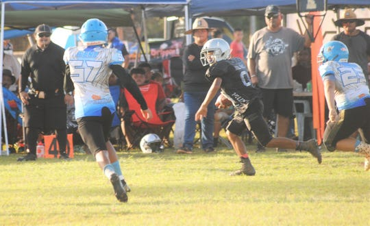 Raiders running back Ryan Blas looks for open field, chased down by Angels No. 57 Vance Meno and No. 23 Harley Tudela during the Matua division championship game Nov. 3 at Southern field.