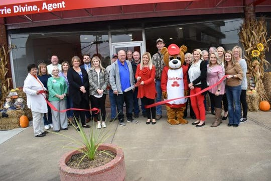 Local State Farm Insurance office owner Carrie Divine cuts the ribbon at her new office on October 29.