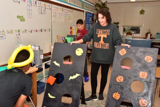 A student enjoys the bean bag toss at the West Haven fall festival on Friday, Oct. 25.