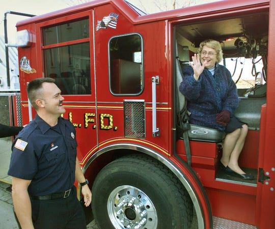 Sonya Margerum waves goodbye as Jim Redd watches before she rides home in a fire truck on Wednesday December 31, 2003. The West Lafayette mayor received the ride home honoring her on her last day in the office. She is retiring after 24 years.