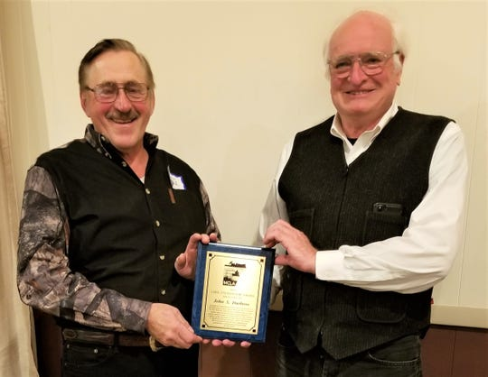 Manitowoc County Lakes Association presented a Lake Stewardship Award at its annual banquet. Tom Ward, left, presents the award to John Durbrow, right, for his years of MCLA leadership as president and past president.