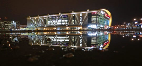 The Fiserv Forum reflects in a puddle of water at the former site of the BMO Harris Bradley Center on Sunday.