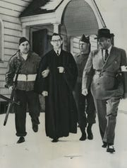"In 'The Wisconsin Story,"" Dennis McCann writes about many curious episodes in state history, such as the simulated Communist takeover of Mosinee on May 1, 1950. In this photo, fake Communist raiders take Rev. Lyle J. Koening, pastor of the Immanuel Evangelical Lutheran Church, into custody."