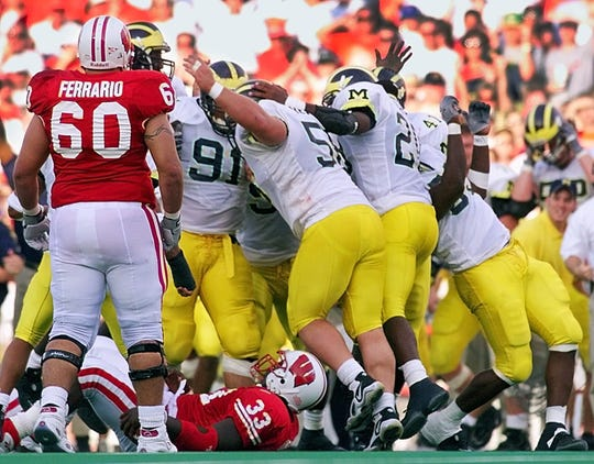 Wisconsin's Ron Dayne (33) lays on the ground as the Michigan defense celebrates a fourth down stop in the fourth quarter Saturday, Sept. 25, 1999, in Madison, Wis. Watching is Wisconsin's Bill Ferrario (60). Michigan won 21-16.