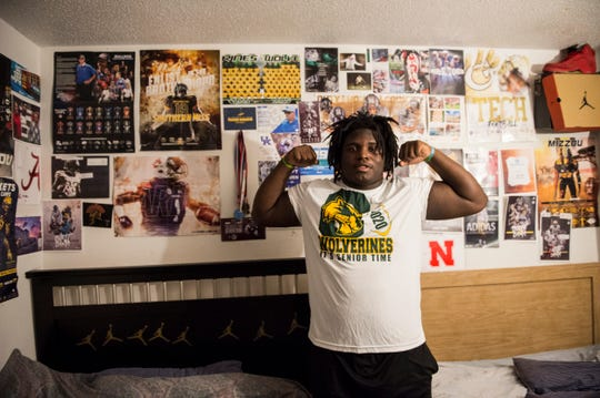 James Robinson pose for a picture in his bedroom in Montgomery, Ala., on Wednesday, Oct. 30, 2019. The wall is filled with posters from various schools that recruited him.