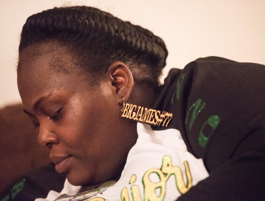 JoAnn Stamps-Conway wears a custom earring for her son, James Robinson, in her homein Montgomery, Ala., on Wednesday, Oct. 30, 2019.