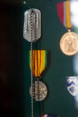 Gary Bonvillian's dog tags and Vietnam Service Medal is displayed in his office, Monday, Nov. 4, 2019, at his home in Estero.