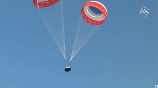 In this image made from a video provided by NASA  parachutes guide the Starliner capsule to the ground after a test of Boeing's crew capsule's launch abort system in White Sands Missile Range in N.M., on Monday, Nov. 4, 2019. The capsule carried no astronauts Monday morning, just a test dummy.