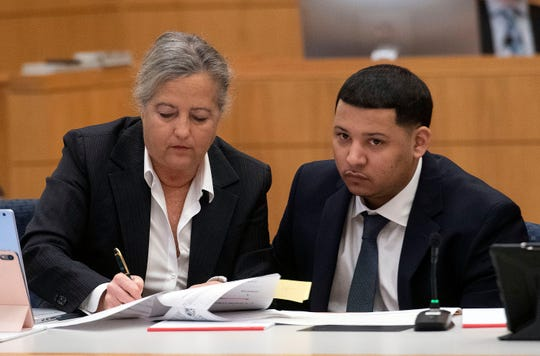 Markquise Wallace looks on as Cheryl Young, a member of his defense team, reviews court documents during jury selection Monday, Nov. 4, 2019.