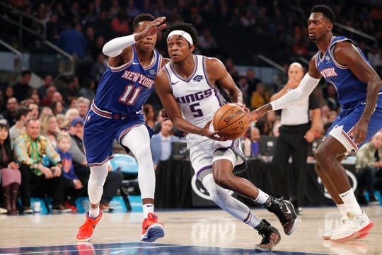 Sacramento Kings guard De'Aaron Fox (5) drives past New York Knicks guard Frank Ntilikina (11) and center Bobby Portis (1) during the first half of an NBA basketball game in New York, Sunday, Nov. 3, 2019. (AP Photo/Kathy Willens)