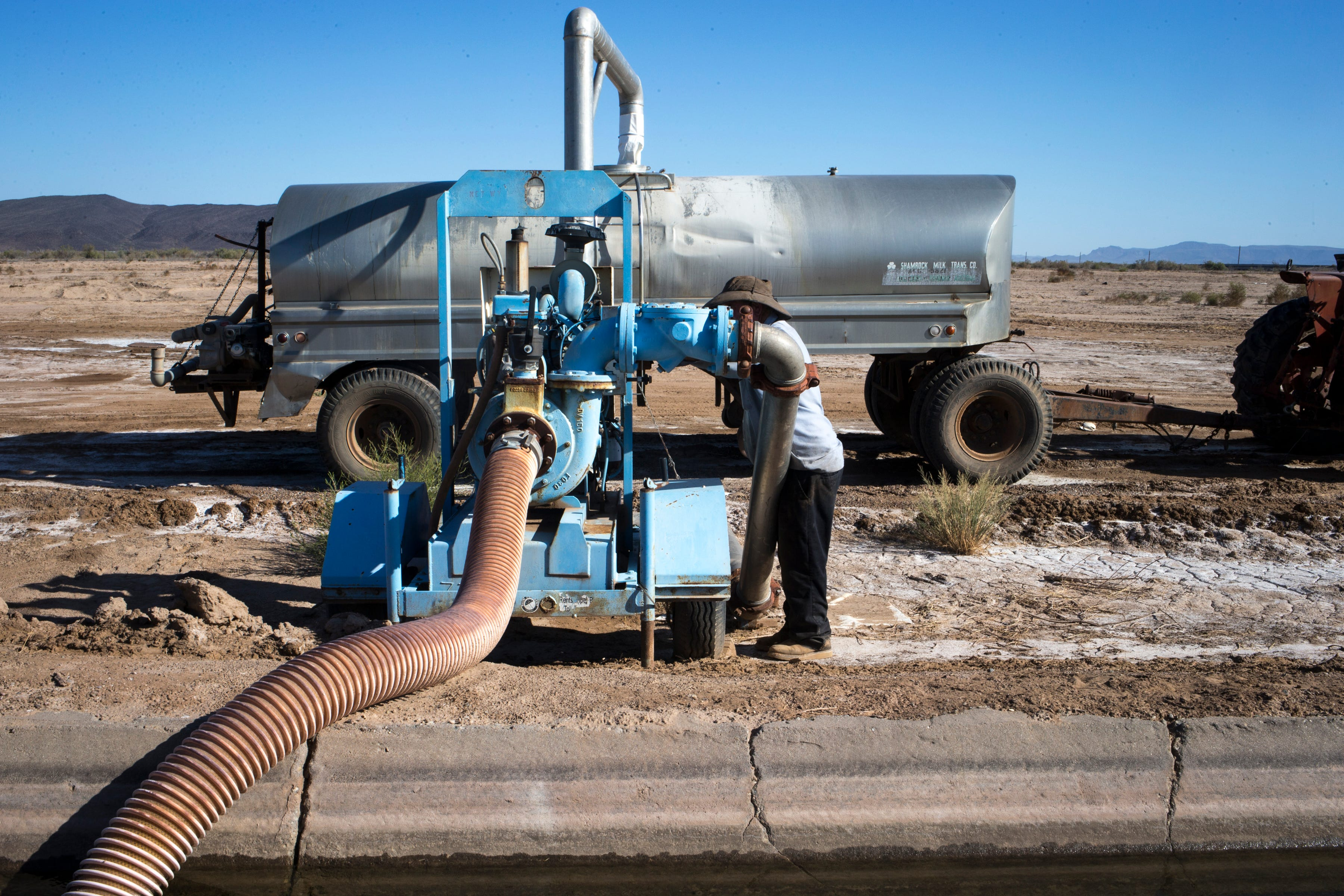 Mark Skousen fills his 3,500-gallon water tank, September 12, 2019, at his farm in Hyder, Arizona. Skousen was watering a road for dust control.