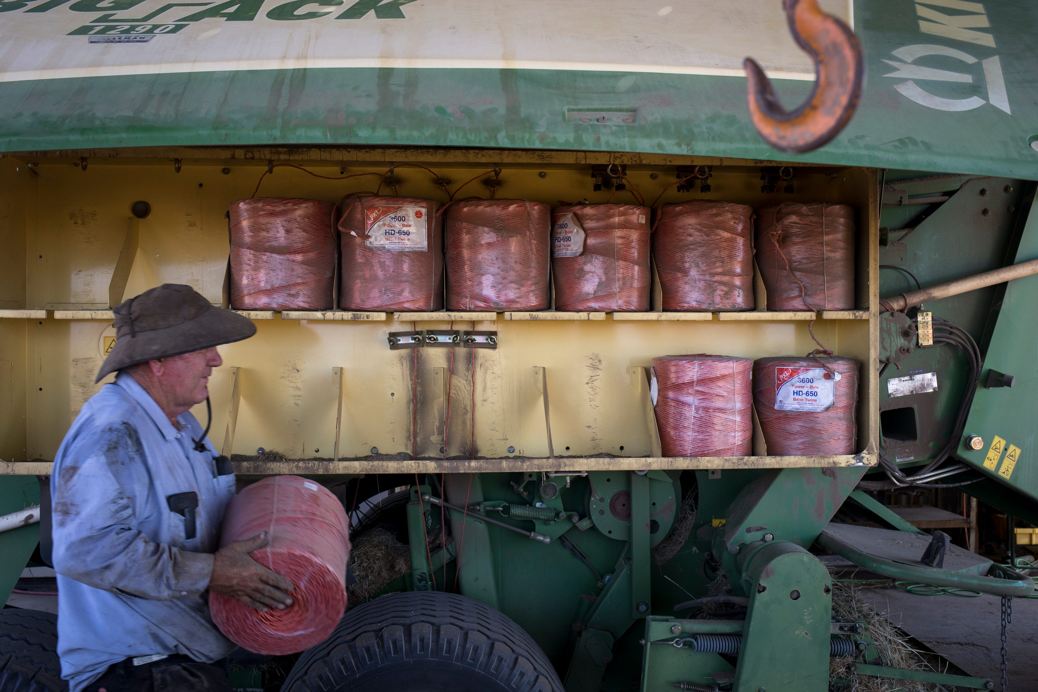 Mark Skousen reloads his hay baler with baling twine, September 12, 2019, while working on his farm in Hidden Valley, Arizona.