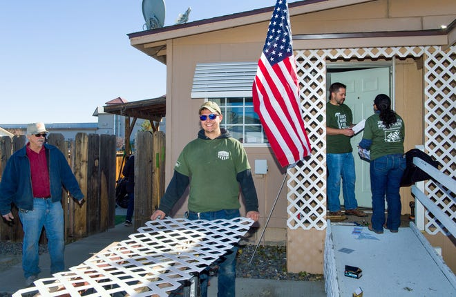 "Home Depot employees Maynard Green of Sparks, left, watches as D.J. Green of Reno (no relation), center, carries lattice while making repairs at veteran Martin Harka's home in Fernley. Several of the Home Depot volunteers who participated in the ""Celebration of Service"" project were veterans, including D.J., an Army veteran who served two tours in Afghanistan, and Maynard's wife, who served 20 years in the Air Force."