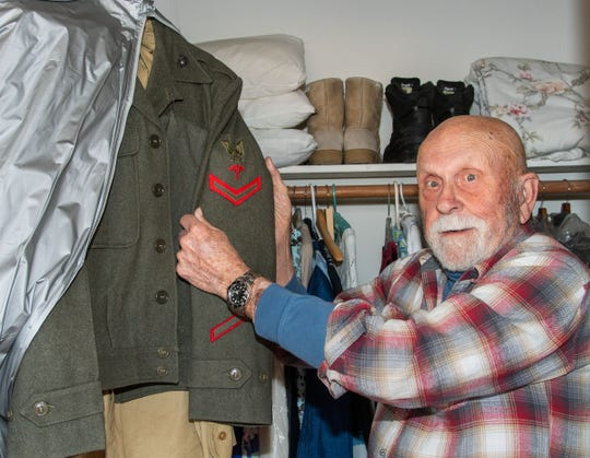 Paul Lunsford shows a patch signifying that he was a Navy medic serving with the Marines in Korea.