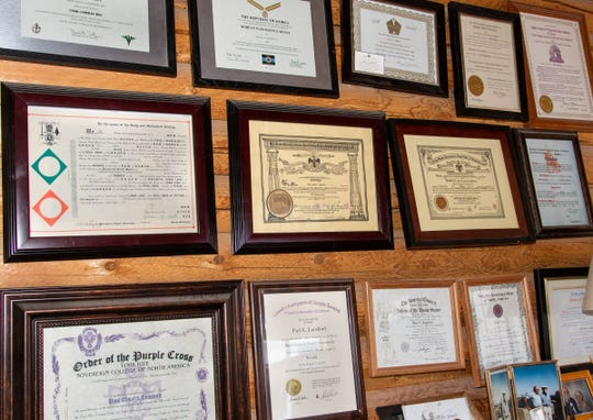A wall in Paul Lunsford's office is covered with degrees, awards and certificates from the military, police force and civic organizations.