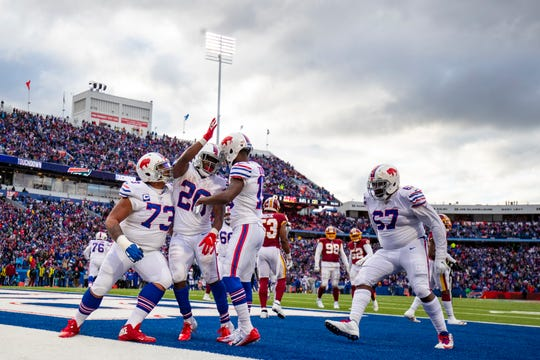 ORCHARD PARK, NY - NOVEMBER 03:  Devin Singletary #26 of the Buffalo Bills celebrates a touchdown carry with Dion Dawkins #73 and John Brown #15 during the fourth quarter against the Washington Redskins at New Era Field on November 3, 2019 in Orchard Park, New York. Buffalo defeats Washington 24-9.  (Photo by Brett Carlsen/Getty Images)