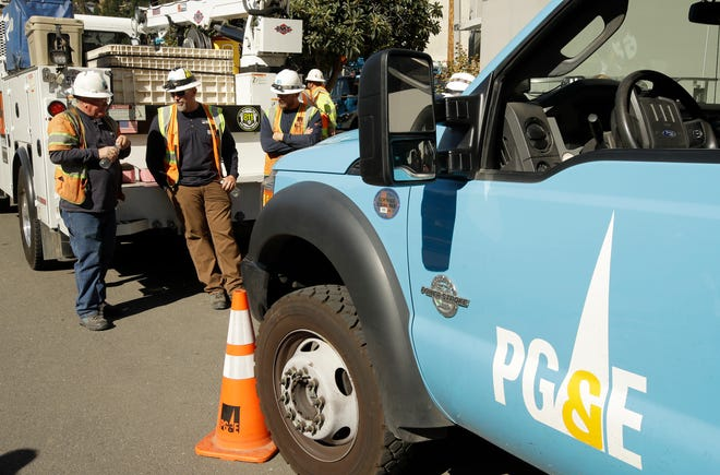 Pacific Gas & Electric and CalTrans workers stand near the Caldecott Tunnel in Oakland, Calif. on Oct. 9, 2019.
