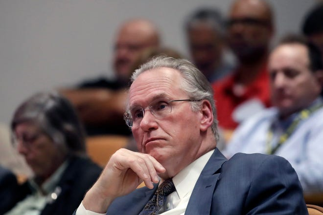 Pacific Gas and Electric Company (PG&E) CEO Bill Johnson listens to speakers during a California Public Utilities Commission meeting in San Francisco, Friday, Oct. 18, 2019. (AP Photo/Jeff Chiu)