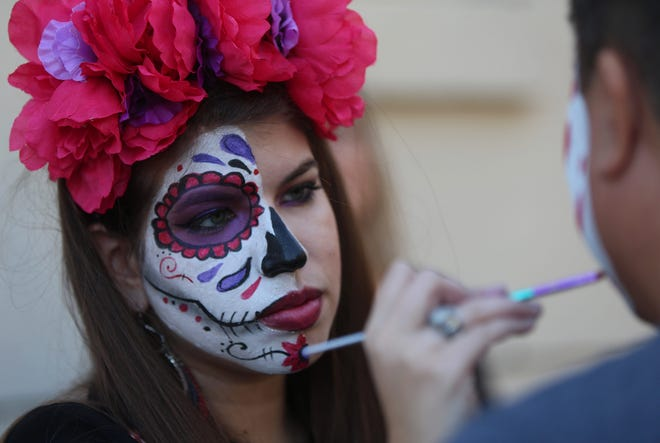 Ashley Perales paints faces during the Dia de los Muertos event at Reynas Tacos in San Angelo on Saturday, Nov. 2, 2019.