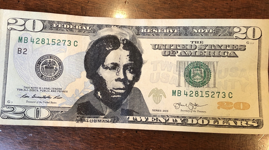 Holly Eckman displays $20 bill with Harriet Tubman's face on it.