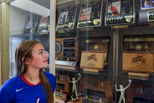 Ava Nilsson looks at the volleyball trophies won by previous Warner setters on Thursday, October 31, outside the high school gymnasium. She remembers looking at the trophy case as a young child and hoping to become just like those girls.
