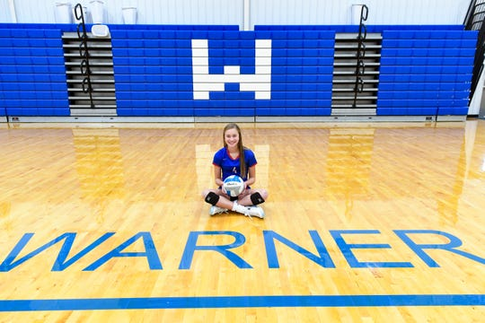 Ava Nilsson sits for a portrait in the Warner High School gymnasium on Thursday, October 31. Nilsson, who is in eighth grade, plays as starting setter on the high school's volleyball team.