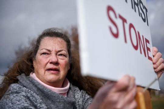 """Elaine Engelgau becomes emotional while sitting behind a cross in protest during the execution of Charles Rhines on Monday, Nov. 4, 2019 at the South Dakota State Penitentiary in Sioux Falls. """"Jesus said he who is without sin cast the first stone,"""" Engelgau said."""