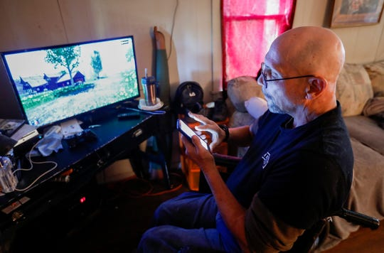 Chuck McClancy checks his phone as he waits for a game to load on his Playstation at his new rental home on Thursday, Oct. 31, 2019. McClancy formerly lived in a Chris Gatley owned property.