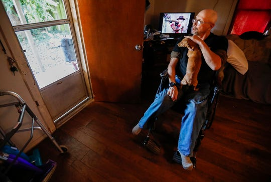 Chuck McClancy pets his dog Bella at his new rental home on Thursday, Oct. 31, 2019. McClancy formerly lived in a Chris Gatley owned property.