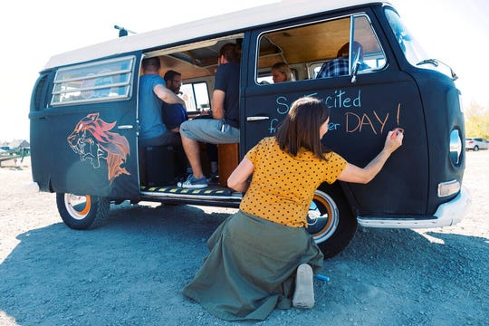 Stacey Squire writes a positive message on one of the doors of the Chalkbus on Saturday, Oct. 26, 2019, in American Fork, Utah. (Michael Schnell/The Daily Herald via AP)