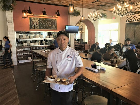 Chef Tommy Hwang holds Eggs Benedict, one of the popular brunch items, at Grove Brunch Café on the West Side.