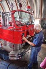 Norman Yeingst, a volunteer with the Wichita Falls Fire and Police Museum, works on re-wiring the headlights of a 1965 Mack open cab fire truck.