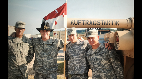 "Shawn Monien shares a photo from 2007 of the guidon and his crew standing in front of his tank dubbed ""Auftragstaktik""."