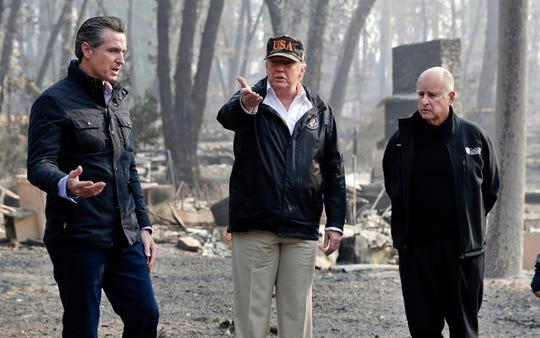 President Donald Trump talks with then gov.-elect Gavin Newsom, left, as California Gov. Jerry Brown listens during a visit to a neighborhood impacted by the wildfires in Paradise, California.
