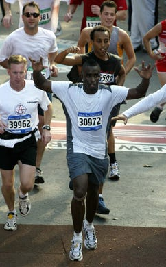 Diddy raises his arms while crossing the finish line of the New York City Marathon on Nov. 2, 2003 in New York.