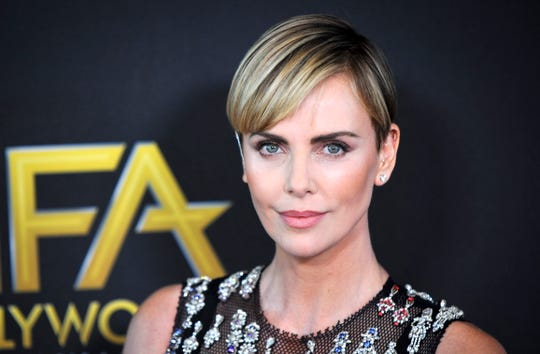 Charlize Theron poses for photographers upon arrival at the 23rd annual Hollywood Film Awards.