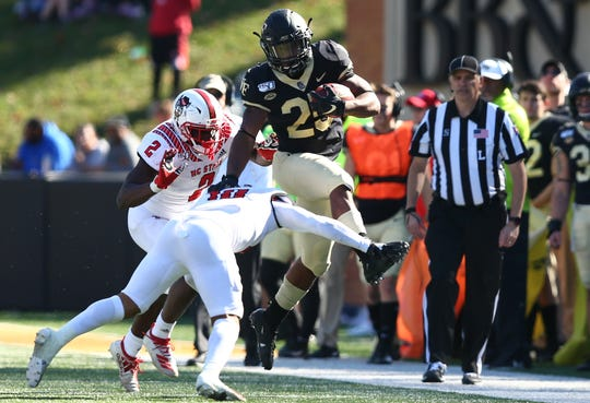 Wake Forest tight end Brandon Chapman hurdles North Carolina State  safety Tanner Ingle in the third quarter at BB&T Field.