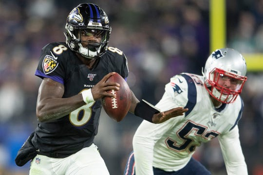 Ravens quarterback Lamar Jackson runs past Patriots linebacker Kyle Van Noy (53) during the fourth quarter at M&T Bank Stadium.